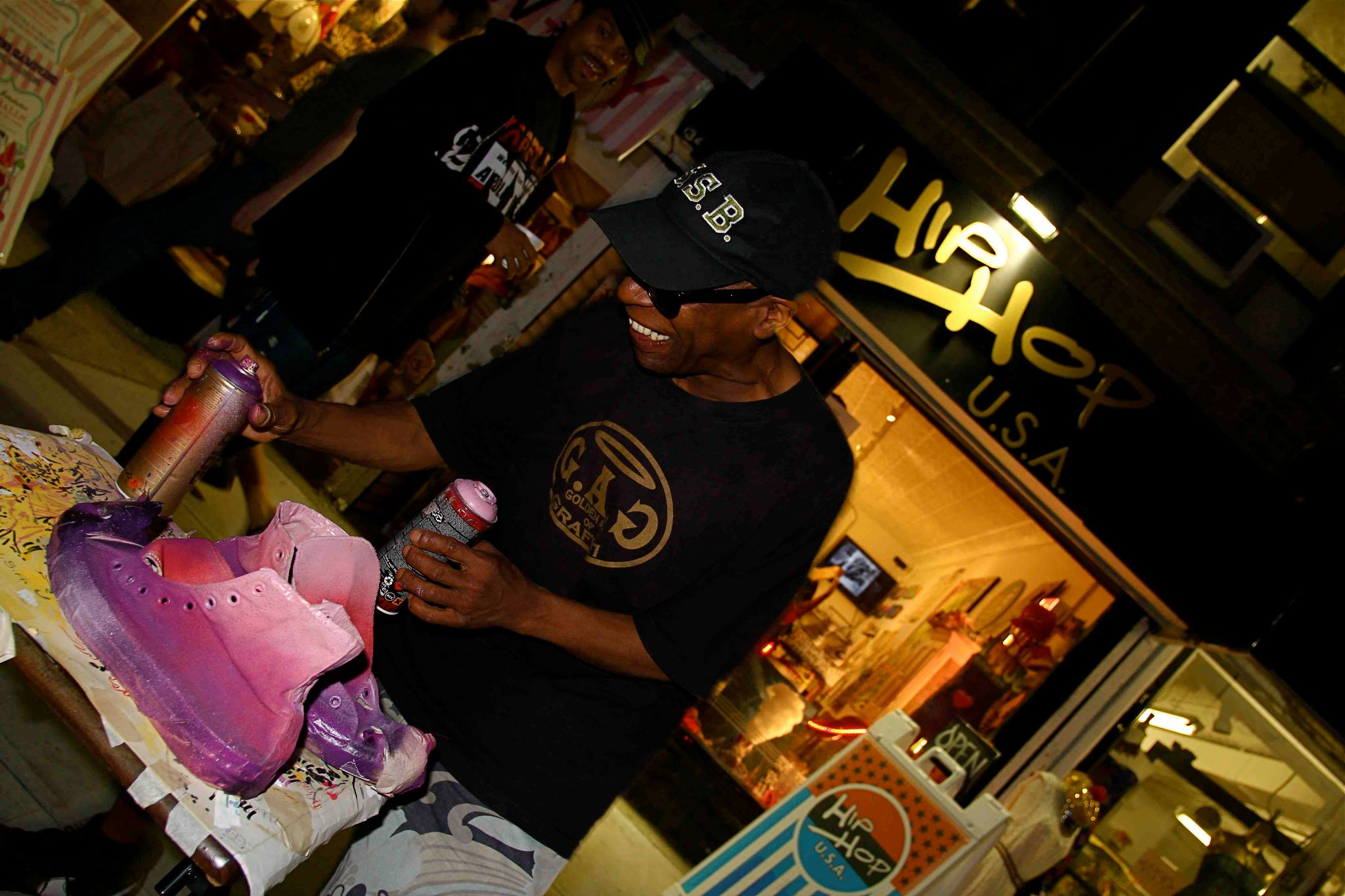 Hip Hop USA store with custom artist, Shadow customizing a sneaker for a shop patron.